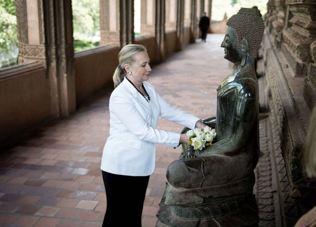 U.S. Secretary of State Hillary Rodham Clinton place flowers at a statue after during a tour of the Ho Phra Keo Temple, in Vientiane, Laos, Wednesday, July 11, 2012. (AP Photo/Brendon Smialowski, Pool)