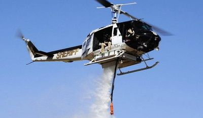 Washoe County Sheriff's Office This HH-1H Huey helicopter, the jewel of the Regional Aviation Enforcement Unit in Washoe County, Nev., failed to act during the Pinehaven wildfire last week because of a tangle of federal rules.