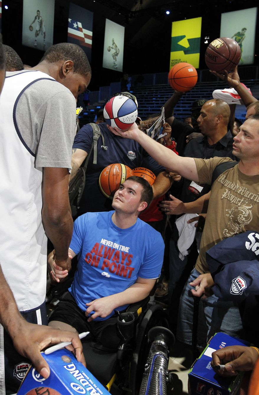 USA Basketball guard Kevin Durant, left, shakes hands with U.S. Army Corporal Cody Stanton after a practice Saturday, July 14, 2012 in Washington. (AP Photo/Alex Brandon)