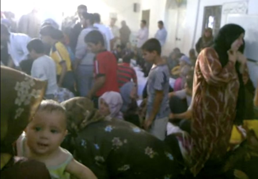 This image made from amateur video from Hama Revolution 2011 and accessed by AP video, Friday, July 13, 2012, purports to show families gathered around bodies of victims killed by violence that, according to anti-regime activists, was carried out by government forces in Tremseh, Syria, about 15 kilometers (nine miles) northwest of the central city of Hama. (AP Photo/ Hama Revolution 2011 via AP video)