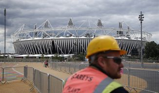 A construction worker stands outside the Olympic Stadium in London as preparations continue on Sunday, July 15, 2012, for the Summer Games. (AP Photo/Jae Hong)