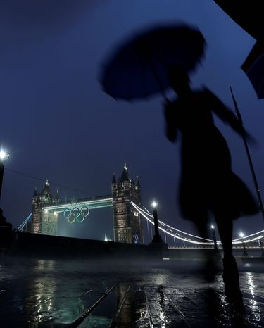 A pedestrian walks in the rain past the Tower Bridge displaying the Olympic rings on Saturday as London prepares for the 2012 Summer Olympics. The last few weeks and days are all about putting up signs, fitting in the remaining seats and completing the landscaping. (Associated Press)