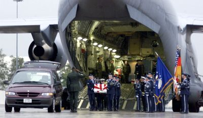 A U.S. Air Force honor guard carries the remains of a killed sailor from a C-17 Air Force aircraft at the U.S. air base in Ramstein, Germany, on Oct. 13, 2000. (U.S. Air Force via Associated Press)