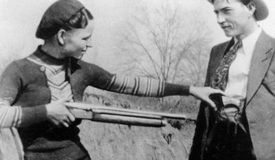 Bonnie Parker playfully holds a gun on boyfriend Clyde Barrow in an undated photo. Guns and personal items they carried on the day they were killed are being sold at auction. (Associated Press)