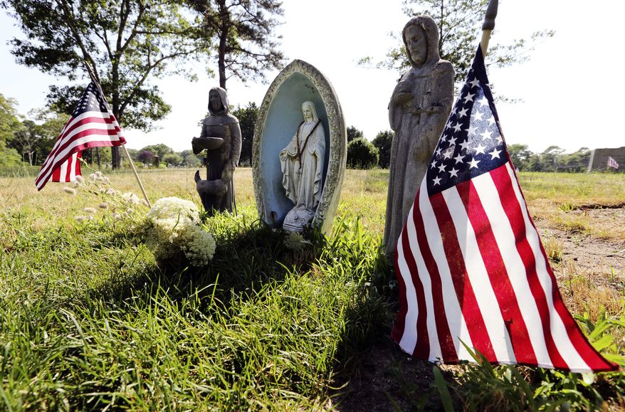 Religious statues and American flags mark the grave to which Mary Richardson Kennedy's body was moved in St. Francis Xavier Cemetery in Centerville, Mass. (AP Photo/Michael Dwyer)