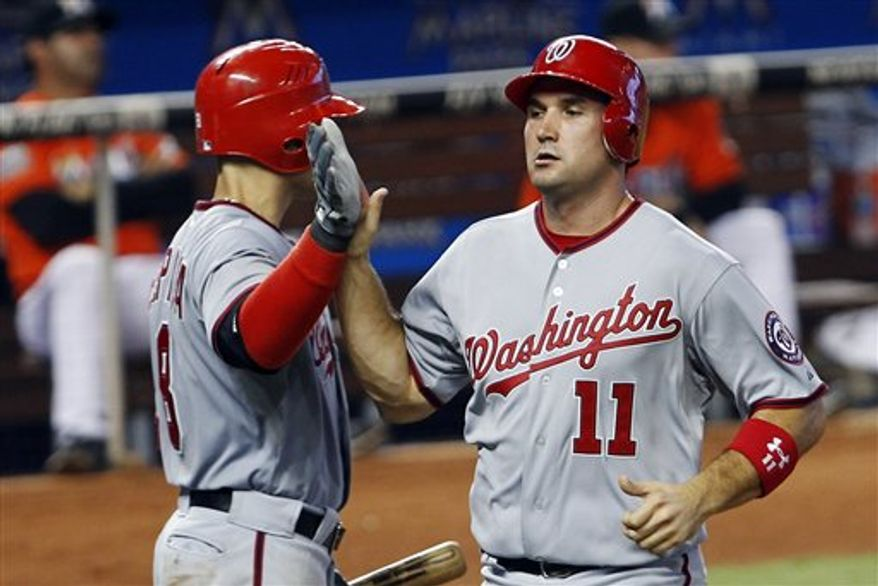 Washington Nationals' Ryan Zimmerman (11) is congratulated by Danny Espinosa after Zimmerman scored on a base hit by Michael Morse against the Miami Marlins in the sixth inning of a baseball game in Miami, Sunday, July 15, 2012. The Nationals won 4-0. (AP Photo/Alan Diaz)