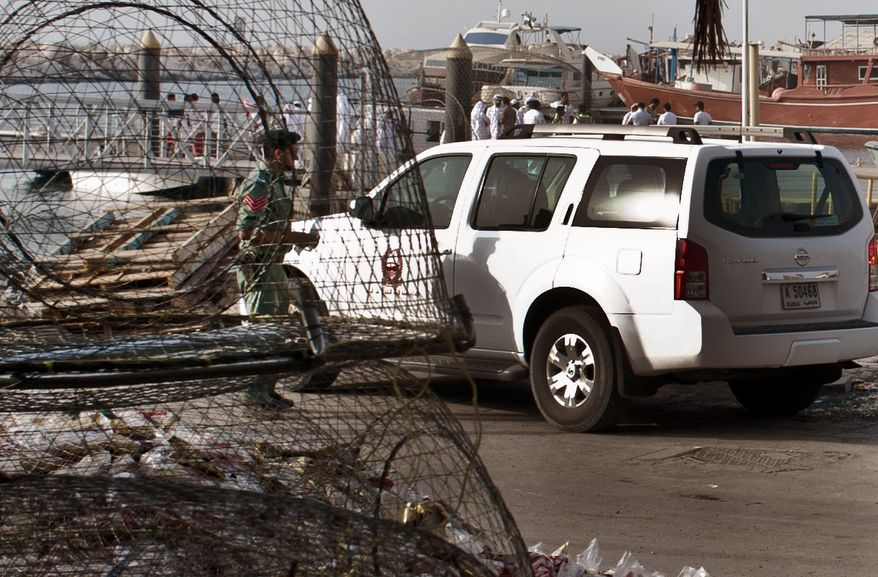Emirati police and other officials inspect a boat docked in a fishing harbor in the Jumeirah district of Dubai, United Arab Emirates, on July 16, 2012. A U.S. official in Dubai said an American vessel fired on a boat off the coast of the United Arab Emirates, killing one person and injuring three. (Associated Press)