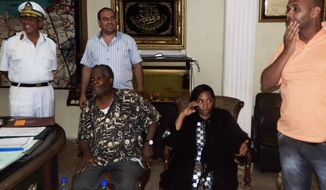 Two American tourists, the Rev. Michel Louis (seated at left) and Lissa Alphonse (seated at right), rest at a police station on Monday, July 16, 2012, after their release by a kidnapper in El Arish, in the northern part of Egypt's Sinai Peninsula. (Associated Press)