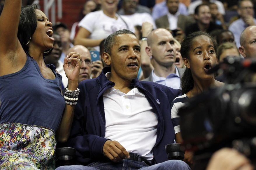 First lady Michelle Obama, from left, President Barack Obama, and daughter Malia Obama react as they watch Team USA and Brazil during the first half of an Olympic exhibition basketball game, Monday, July 16, 2012, in Washington. (AP Photo/Alex Brandon)
