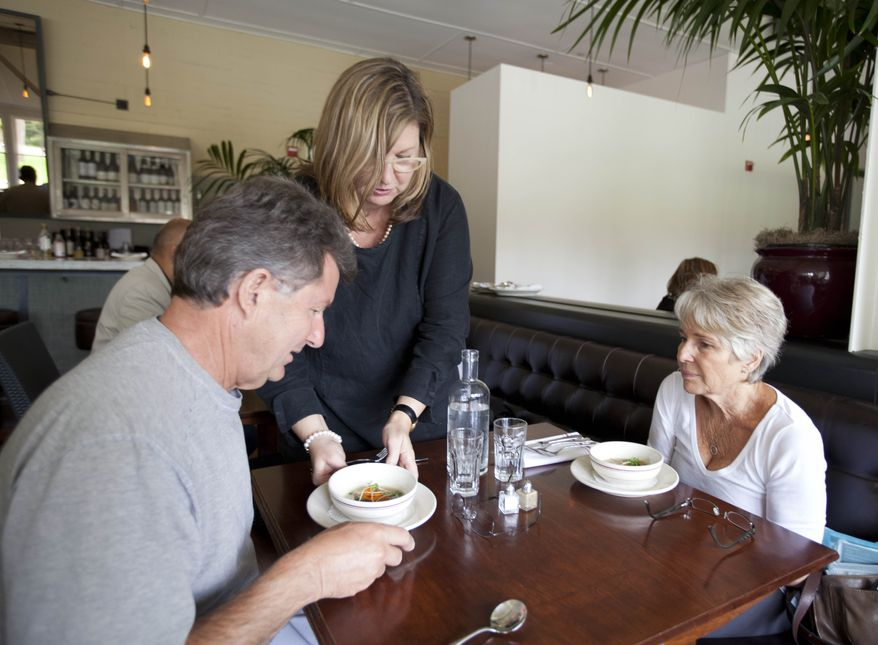 Maureen Donegan, center, serves Aromatic Foie Gras soup to Gene Mattiuzzo, left, and his wife Sue Ann, right, of Fort Bragg, Calif., during lunch at the Presidio Social Club restaurant Tuesday, July 17, 2012 in San Francisco.  (AP Photo/Eric Risberg)
