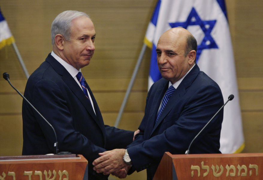 ** FILE ** Israeli Prime Minister Benjamin Netanyahu (left) and Kadima Party leader Shaul Mofaz shake hands before holding a joint press conference to announce the new coalition government in Jerusalem on Tuesday, May 8, 2012. (AP Photo/Sebastian Scheiner)