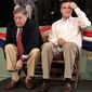 ** FILE ** Republican presidential candidate Mitt Romney (right) prepares to speak on Friday, Nov. 3, 2011, at the town hall in Exeter, N.H., as former Gov. John Sununu pulls up his socks. (Associated Press)