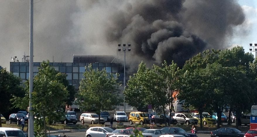 Smoke rises after an explosion at the airport outside the Black Sea resort city of Burgas, Bulgaria, some 250 miles east of the capital, Sofia, on Wednesday, July 18, 2012. The blast killed 4 people and wounded at least 24 more. (AP Photo/Burgasinfo)