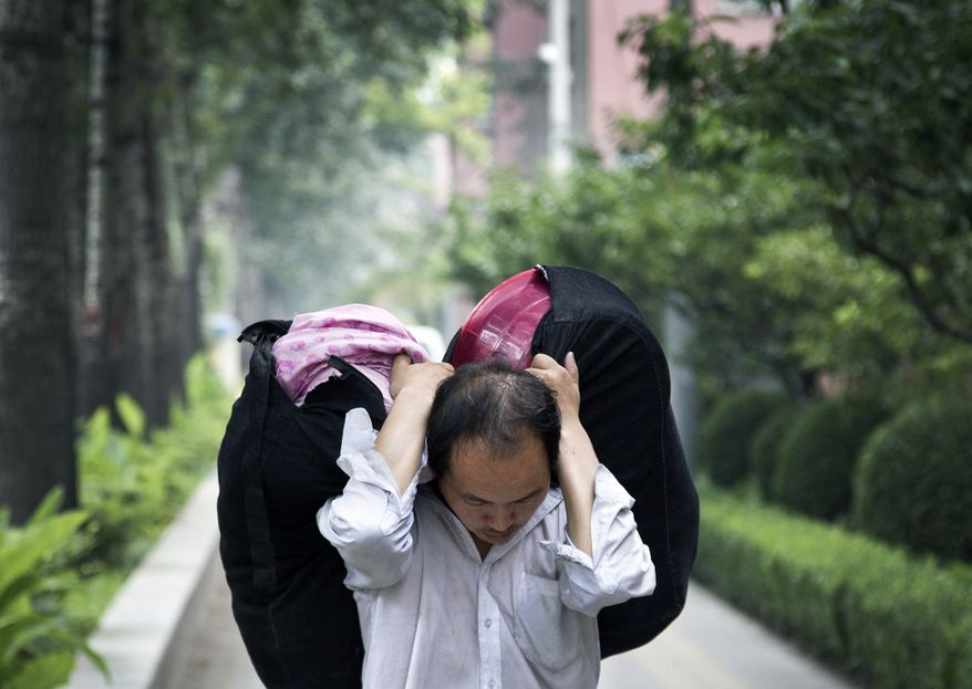 "A migrant worker carries his belongings while walking in Beijing, China Wednesday, July 18, 2012. Premier Wen Jiabao said Tuesday China's employment situation ""will become more complex and severe"" and promised to generate jobs, according to a Cabinet statement, adding to suggestions Beijing might launch new stimulus efforts. (AP Photo/Andy Wong)"