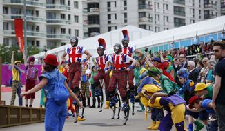Members of the National Youth Theatre perform during the Olympic Team Welcome Ceremony at the Olympic Village for the 2012 Summer Olympics, Tuesday, July 17, 2012, in London. Opening Ceremonies for the London Olympics will be held Friday July 27, 2012. (AP Photo/Jae C. Hong)