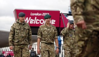 British military personnel walk July 18, 2012, near the Aquatics Center at the Olympic Park in London. Opening ceremonies for the London Olympics will be held July 27, 2012. (Associated Press)