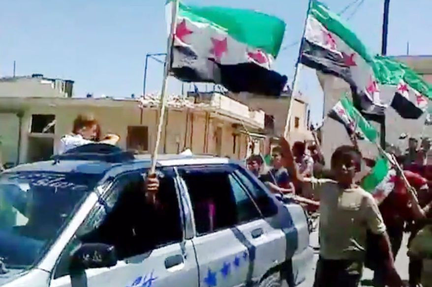 In this image made from amateur video released by the Shaam News Network and accessed July 18, 2012, Syrians celebrate after hearing about the suicide attack that hit the National Security building in Idlib, Syria. The bomb ripped through a high-level security meeting, killing the defense minister as well as President Bashar Assad's brother-in-law. (Associated Press/Shaam News Network via AP video)