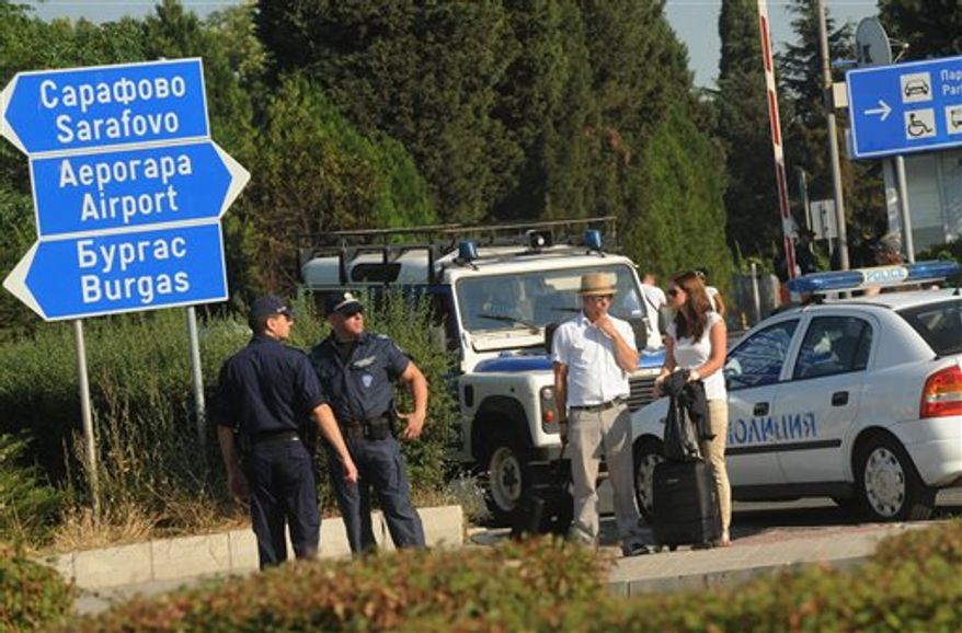 Foreign tourists wait to pass as police block the entrance of Burgas airport, Bulgaria, Thursday, July 19, 2012 a day after a deadly suicide attack on a bus full of Israeli vacationers. A daytime bombing that killed eight people and injured dozens on a bus full of Israeli tourists was most likely a suicide attack, Bulgaria's interior minister said Thursday. He said the suspected attacker was carrying a Michigan driver's license that was being sent to the FBI for authentication. (Associated Press)