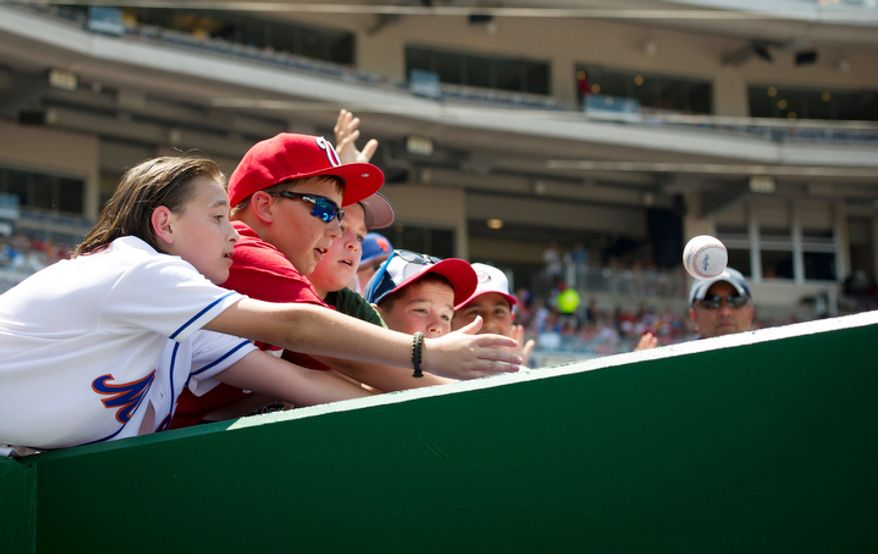 Kids reach out for a tossed ball from the dugout as the Washington Nationals host the New York Mets at Nationals Park in Washington, D.C., Thursday, July 19, 2012. (Rod Lamkey Jr./The Washington Times)