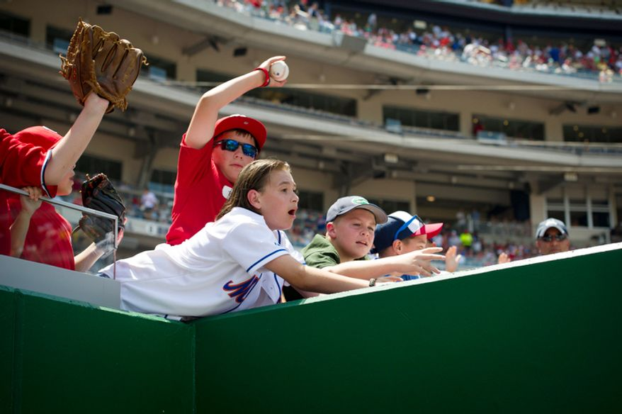 A boy beats others to the ball as he catches a tossed ball from the dugout as the Washington Nationals host the New York Mets. (Rod Lamkey Jr./The Washington Times)