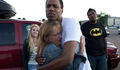 Judy Goos hugs her daughter's friend, Isaiah Bow, 20, while eyewitnesses Emma Goos (left), 19, and Terrell Wallin, 20, gather July 20, 2012, outside Gateway High School in Aurora, Colo., where witnesses were brought for questioning after a gunman fired into a crowded movie theater, killing at least 12 people and injuring at least 50 others. (Associated Press)