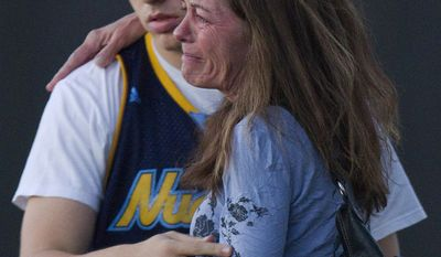Jacob Stevens, 18, hugs his mother Tammi Stevens after being interviewed July 20, 2012, by police outside Gateway High School in Aurora, Colo., where witness were brought for questioning after a shooting at a movie theater. (Associated Press)