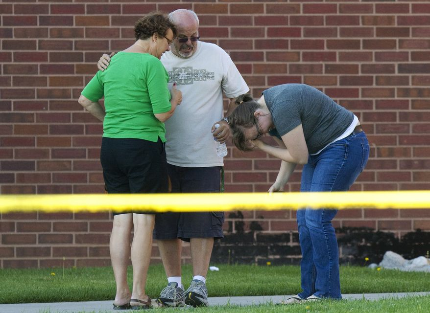 Tom Sullivan (center) stands with family members July 20, 2012, outside Gateway High School in Aurora, Colo., where witness were brought for questioning after a gunman opened fire in a crowded movie theater, killing 12 people and injuring at least 50 others. (Associated Press)