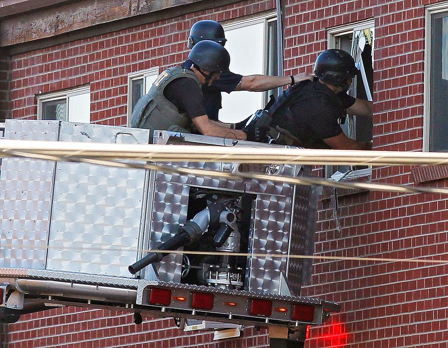 Police use a video camera July 20, 2012, in Aurora, Colo., to look inside an apartment of the suspect in a shooting at a movie theater. As many as 12 people were killed and 50 injured at a shooting at the Century 16 movie theater in Aurora earlier that morning during the showing of the latest Batman movie. (Associated Press)