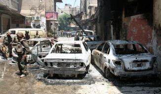 In this photo taken during a government-organized tour, Syrian soldiers stand July 20, 2012, next to burned cars after they regained control of the district of Midan, in the southern part of Damascus, Syria. (Associated Press)