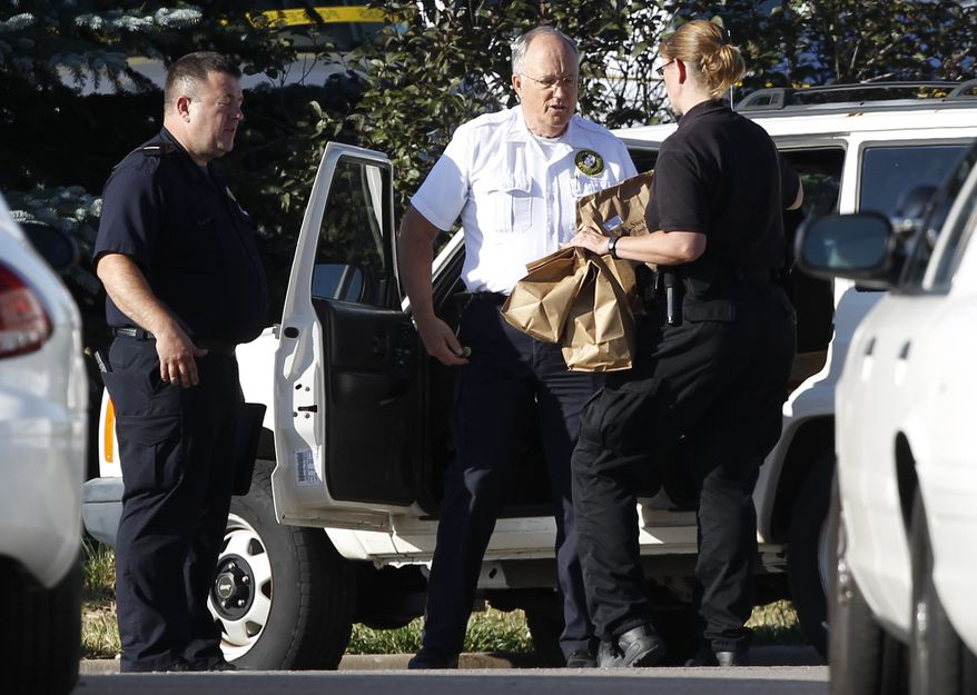 "Officers load bags of evidence into a car outside the Century 16 theater east of the Aurora Mall in Aurora, Colo., on July 20, 2012. A shooting took place in the theater in which at least 12 people died and scores were injured during the premiere showing of ""The Dark Knight Rises."" (Associated Press)"