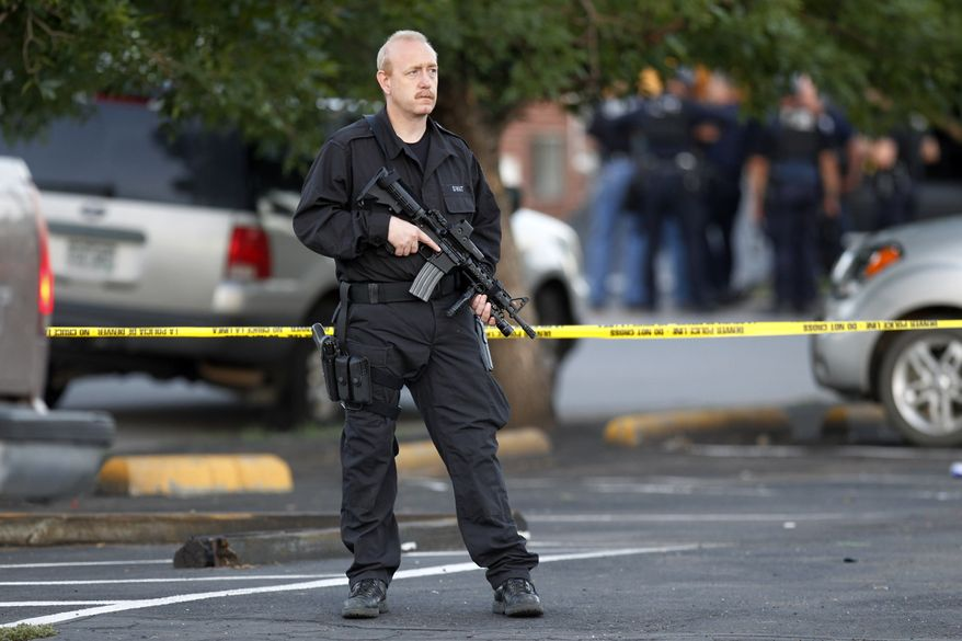 A SWAT team officer stands watch July 20, 2012,  in Aurora, Colo., near an apartment house where the suspect in a shooting at a movie theater lived. As many as 14 people were killed and 50 injured at a shooting at the Century 16 movie theater during the showing of the latest Batman movie. (Associated Press)