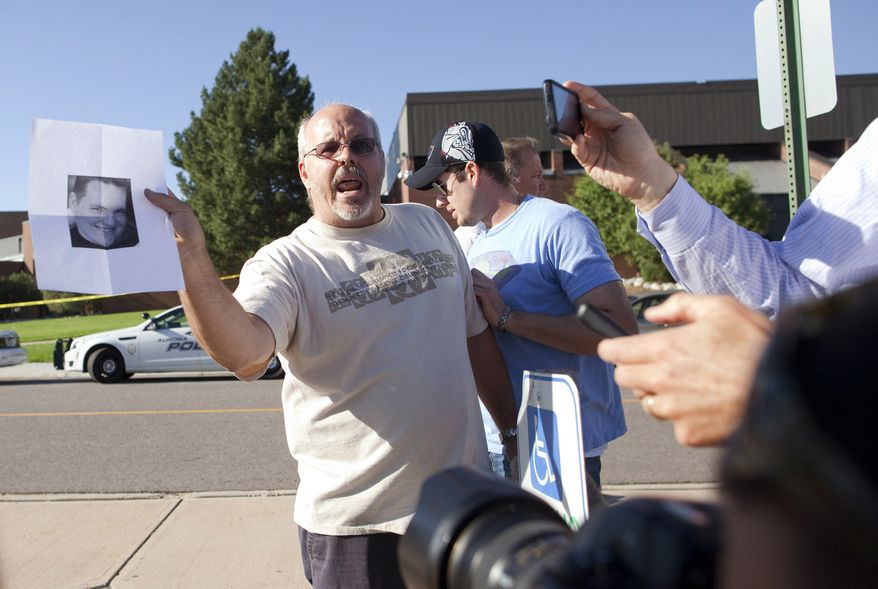 Tom Sullivan holds a photograph of his son, Alex,  outside Gateway High School in Aurora, Colo., on July 20, 2012, as he pleads with the media to help him find his son. Alex Sullivan was celebrating his 27th birthday by attending midnight premiere of the Batman movie Friday night. A gunman wearing a gas mask set off an unknown gas and fired into the crowded movie theater killing 12 people and injuring at least 50 others, authorities said. (Associated Press)