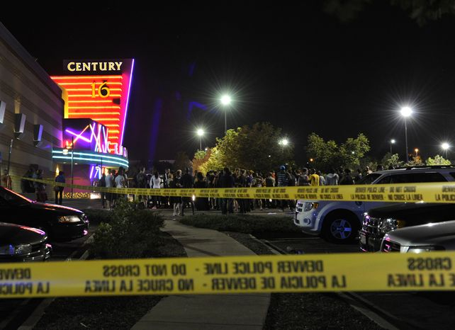 "People gather early morning July 20, 2012, outside the Century 16 movie theater in Aurora, Colo., at the scene of a mass shooting in which 14 people were killed and 50 others were injured. Police said a gunman appeared at the front of the theater where the latest Batman movie ""The Dark Knight Rises"" was playing and opened fire. (Associated Press/The Denver Post)"