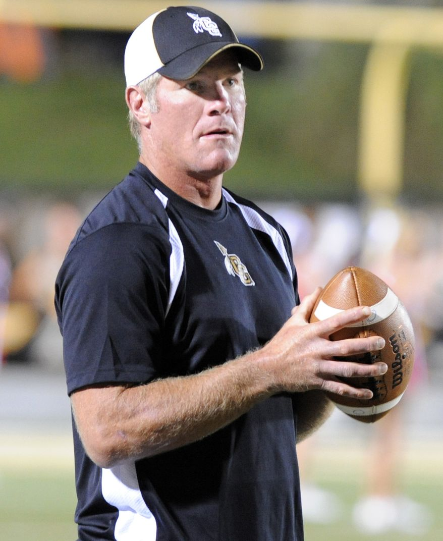 """FILE - In this Sept. 30, 2011, file photo, Oak Grove volunteer coach BrettFavre holds a football on the sidelines as they take on Petal during a high school football game in Hattiesburg Miss. Favre's agent says the former NFL quarterback will be an assistant coach at a Mississippi high school this fall. Bus Cook told The Associated Press Friday, July 20, 2012, that Favre will work at Oak Grove High School this fall """"to help out in some capacity, but I'm not sure exactly what his role will be."""" (AP Photo/ Hattiesburg American, Ryan Moore, File) NO SALES"""
