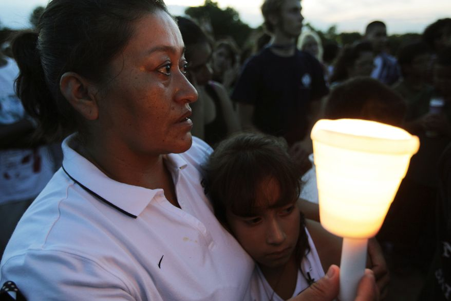 Maria Davila holds her daughter Alexia, 9, during a candlelight vigil on July 20, 2012, in Aurora, Colo., across the street from the movie theater where a gunman killed at least 12 people and wounded dozens of others in one of the deadliest mass shootings in recent U.S. history. (Associated Press)