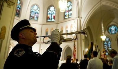 """Paul Lindemann (left) with the U.S. Capitol Police plays """"Taps"""" following the reading of the names of the officers who were killed in the line of duty in 2011 during the annual Blue Mass honoring law enforcement and public safety officials on May 8, 2012 at St. Patrick's in the City in D.C. (Barbara L. Salisbury/The Washington Times)"""