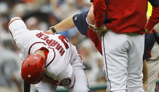 Washington Nationals Bryce Harper reacts to being hit by a foul tip as manager Davey Johnson and a trainer stand by during the first inning of the first baseball game of a doubleheader against the Atlanta Braves, Saturday, July 21, 2012, in Washington.  (AP Photo/Carolyn Kaster)