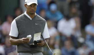 Tiger Woods looks at his scorecard on the sixth green at Royal Lytham & St Annes golf club during the third round of the British Open on Saturday, July 21, 2012. (AP Photo/Tim Hales)