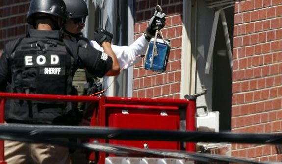"** FILE ** Members of law enforcement wearing body armor and helmets prepare to what ATF sources describe as a ""water shot"" in the apartment of alleged gunman James Holmes Saturday, July 21, 2012 in Aurora, Colo. (AP Photo/Alex Brandon)"