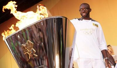 The LOCOG handout photo shows torchbearer Fabrice Muamba lightning the cauldron on the Torch Relay leg between the London Boroughs of Tower Hamlets and Hackney Saturday, July 21, 2012. The Flame arrives at the Olympic stadium for the Opening Ceremony on July 27, 2012.  (AP Photo/LOCOG,  Joe Giddens)