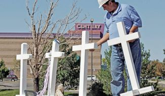 ** FILE ** Greg Zanis of Aurora, Ill., places 12 crosses, one for each shooting victim, across the street from the Century 16 movie theater in Aurora, Colo., on Sunday, July 22, 2012. (Associated Press)