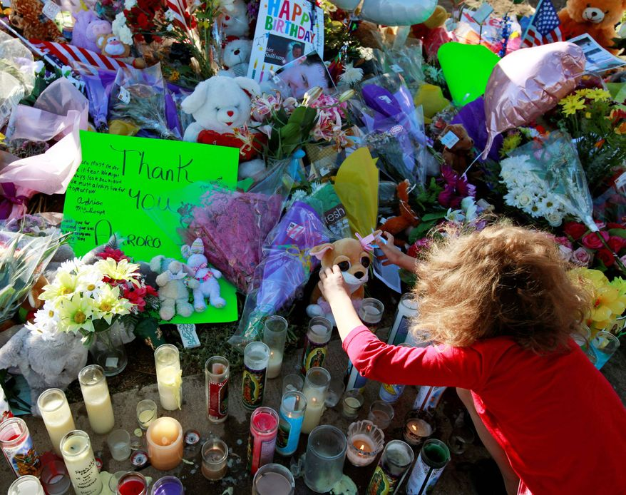 Serenity Brydon, 7, on Sunday places a rosary at a memorial near the Century 16 movie theater in Aurora, Colo. Twelve people were killed and 58 were injured in a shooting attack early Friday. (Associated Press)