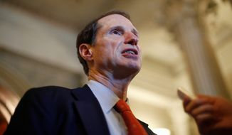 Sen. Ron Wyden, Oregon Democrat, speaks to reporters after leaving the floor of the Senate on Capitol Hill in Washington, Thursday, April 14, 2011. (AP Photo/Charles Dharapak)