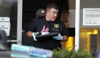 """Investigators remove computer equipment as evidence from the apartment of alleged gunman James Holmes, Saturday, July 21, 2012, in Aurora, Colo. Authorities reported that 12 died and more than three dozen people were shot during an assault at a movie theater midnight premiere of """"The Dark Knight Rises."""" (AP Photo/Alex Brandon)"""