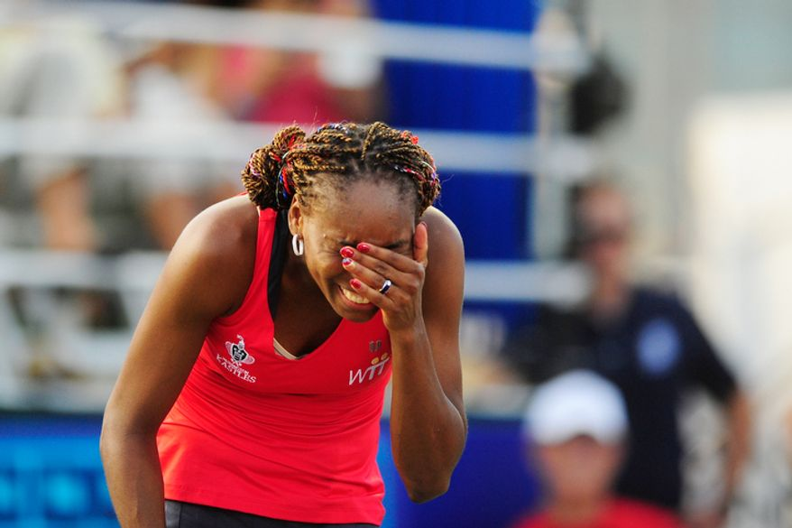 Venus Williams reacts after hitting her doubles partner Anastasia Rodionova while playing in a World Team Tennis match between the Washington Kastles and the Kansas City Explorers.  (Ryan M.L. Young/The Washington Times)