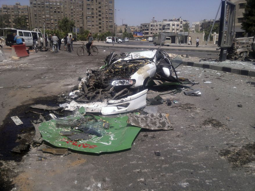 This citizen journalist image shows a destroyed car on a street damaged by tank treads after fighting between rebels and Syrian troops in the Yarmouk camp for Palestinian refugees in south Damascus, Syria, Saturday, July 21, 2012. This week, fierce fighting between troops and rebels reached the Syrian capital, the central bastion of Bashar Assad's rule, shattering parts of the city and sending thousands of people fleeing to neighboring Lebanon and Iraq. Activists and residents reported a tense calm in Damascus Saturday but said sporadic gunfire and explosions could be heard throughout the night. (AP Photo)