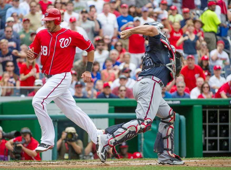 Nationals' Michael Morse scores on a Danny Espinosa RBI single in the bottom of the third inning as Braves catcher Brian McCann can't make the tag. (Rod Lamkey Jr./The Washington Times)