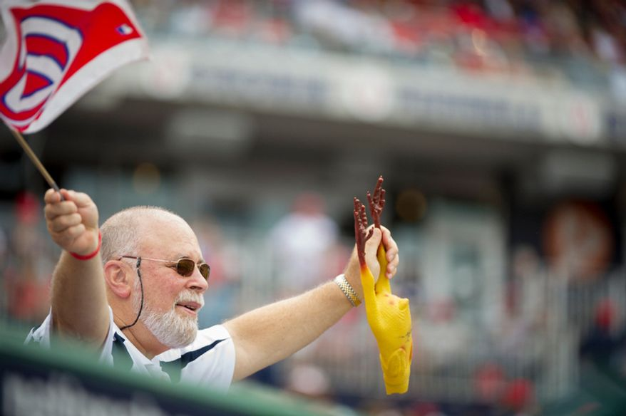 A man waves a Nationals flag and a rubber chicken above the Nationals' dugout . (Rod Lamkey Jr./The Washington Times)