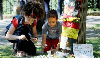 Young fans of singer-songwriter Amy Winehouse light candles for her outside her house in London on Monday, marking the first anniversary of her death. (Associated Press)