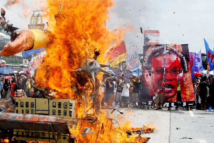 Protesters burn an effigy of Philippine President Benigno Aquino III during a rally at suburban Quezon City northeast of Manila on Monday to protest his third State of the Nation address. Police secured the House of Representatives, where Mr. Aquino spoke. Several people were injured when riot police clashed with thousands of left-wing and trade union protesters who were seeking higher wages, land reform and a halt to alleged human rights violations. (Associated Press)